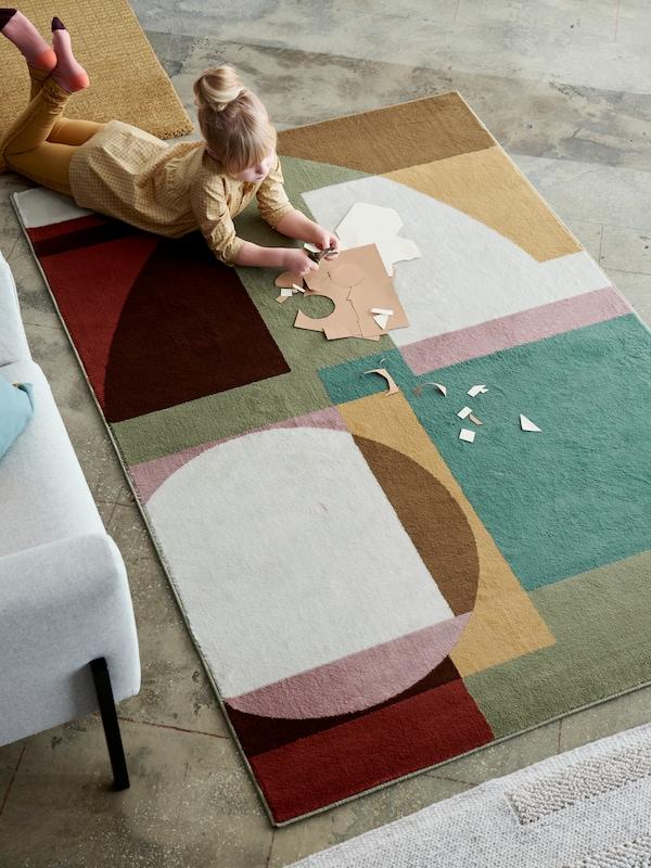 Fillette faisant du bricolage sur un tapis STENMÄTARE de style Bauhaus aux tons pastel placé près d'un canapé.