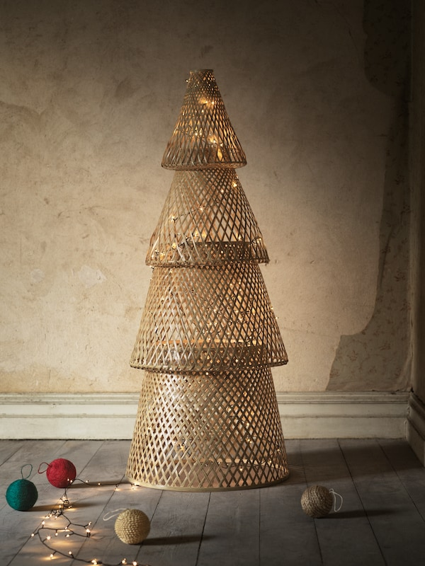 A VINTER 2020 holiday tree made of bamboo shapes stands in a living room, lit up by a chain of decorative lights.