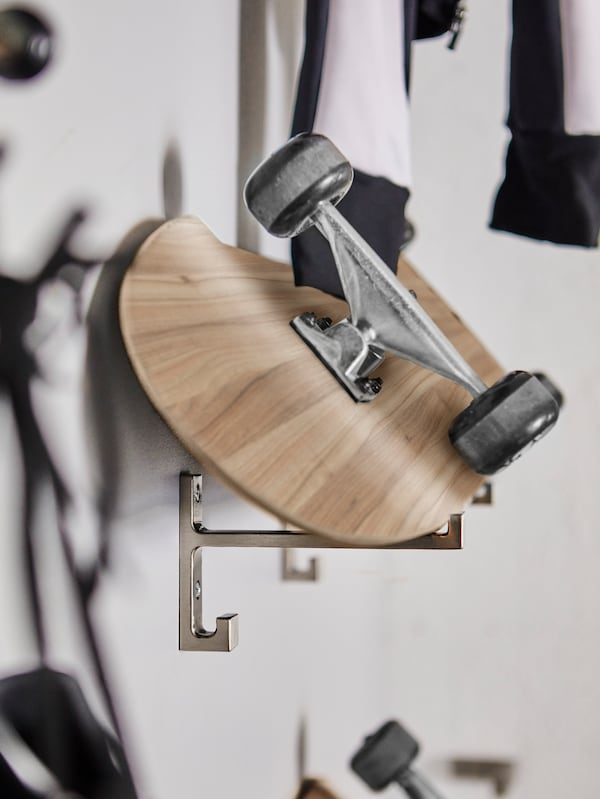 A skateboard leaning against the wall supported by two BJÄRNUM hooks made of aluminum.