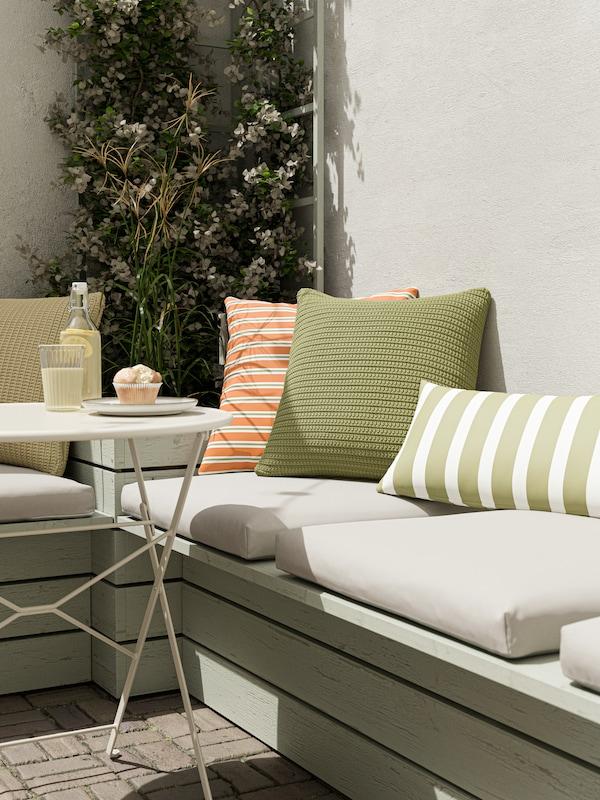 Una panchina all'esterno con cuscini per sedia da esterno KUDDARNA e cuscini da interno/esterno di diversi colori e motivi.
