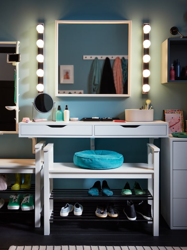 A white EKBY ALEX wall shelf with drawers and make-up products on top, plus a white mirror with wall lights on each side.