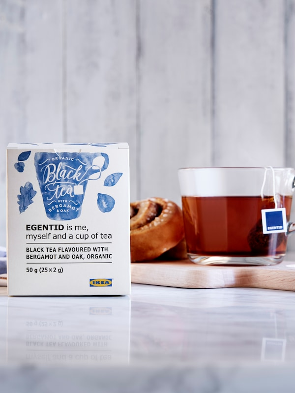 Cinnamon roll and tea in glass cup on small tray, in turn placed on a section of marble worktop; packet of tea on the side.