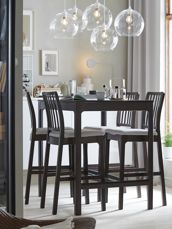 A pale grey room with five clear pendant lamps hanging above a black EKEDALEN bar table and four black bar chairs.