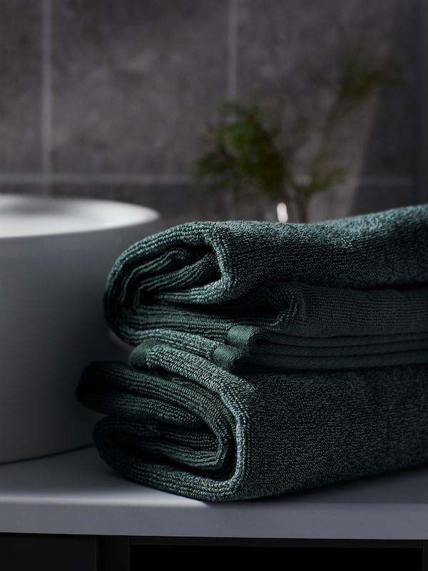 Pænt foldede HIMLEÅN håndklæder i meleret mørkegrøn danner en lille stabel ved siden af en håndvask i et badeværelse med grå fliser.