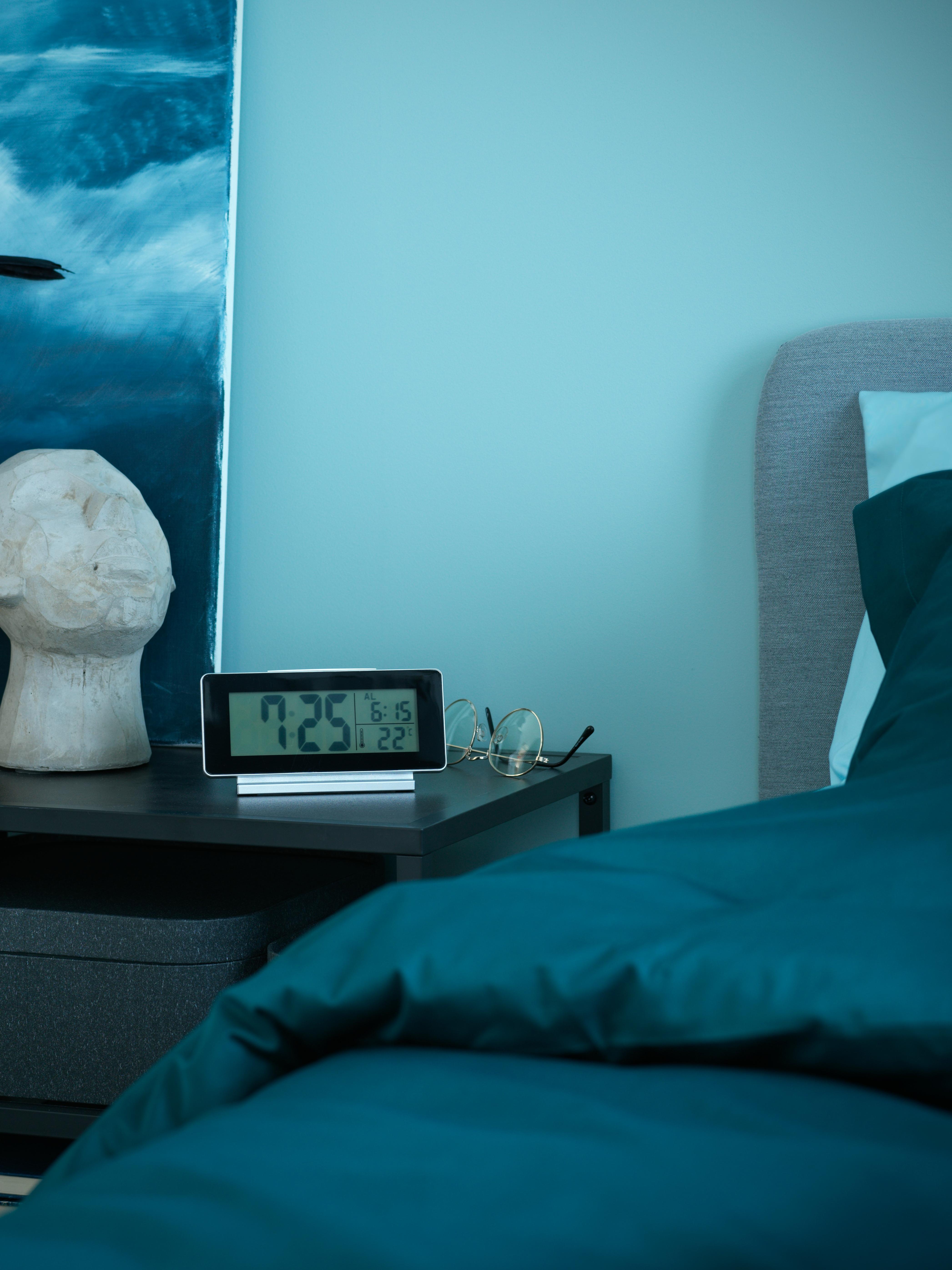 FILMIS sat/termometar/alarm crne boje na noćnom ormariću pored male kamene biste i ispred slike.