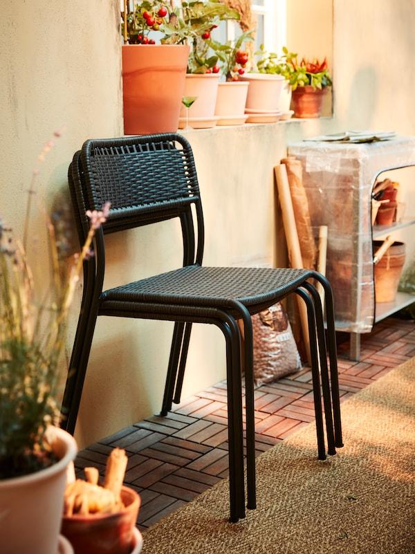 Drei übereinander gestapelte Gartenstühle vor einer gelben Wand, u. a. mit einem flach gewebten Teppich, einem Regal und Pflanzen in Terracottatöpfen.