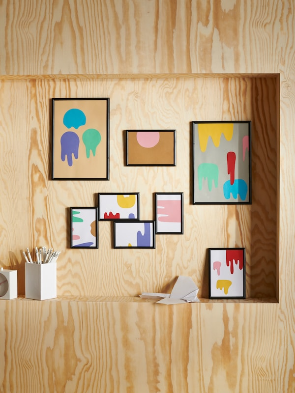 A wooden wall with lots of pictures in picture frames of different sizes, and a ledge with a frame and a box of pencils.