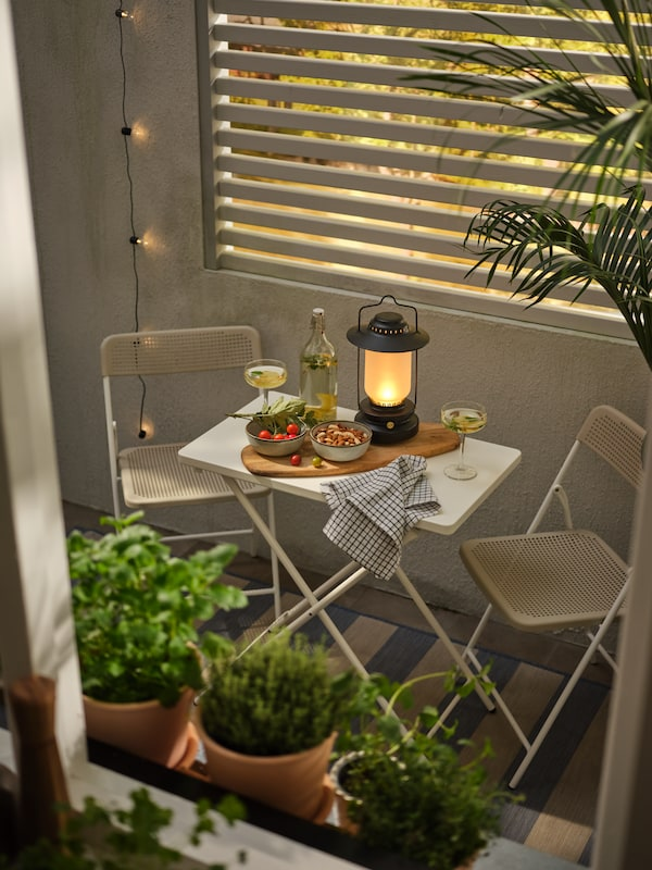 A white/beige TORPARÖ dining set with refreshments, a cutting board and a STORHAGA table lamp on top, and plants all around.