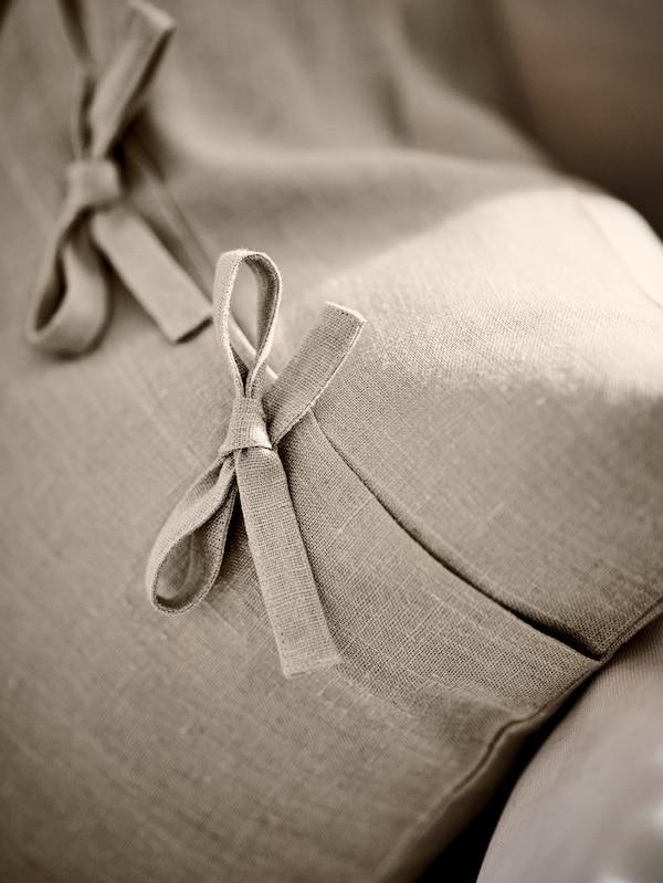 L'arrière d'un coussin AINA beige sur un canapé couleur crème, montrant deux des attaches nouées.