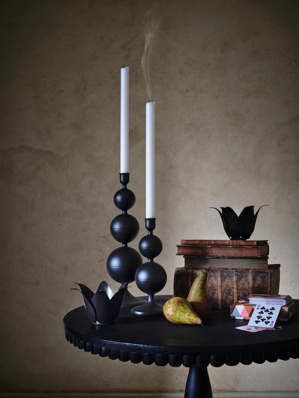 Two black DEKORERA candle sticks stand on a black table, with pears and books piled up next to it.