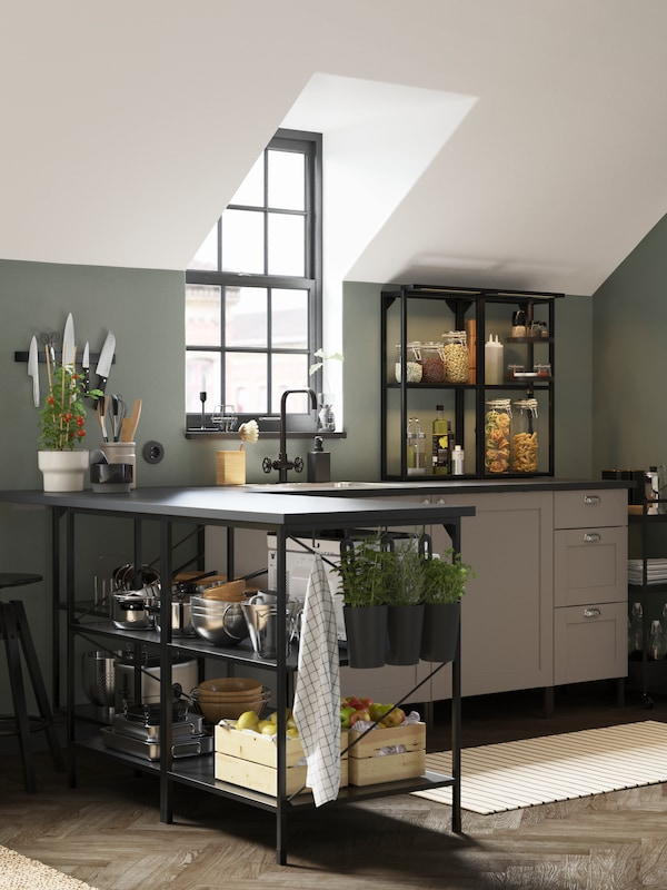 An ENHET kitchen combination with a mix of black open shelves and grey closed cabinets and drawers, and a kitchen island.