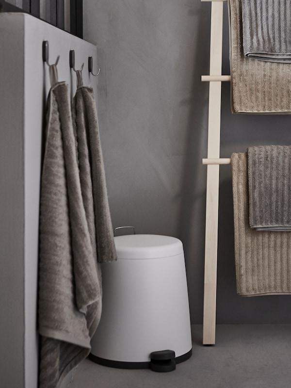 Un coș cu pedale SNÄPP între un stand de prosoape de mesteacăn VILTO și trei cârlige de perete care țin prosoape, în colțul unei camere gri.