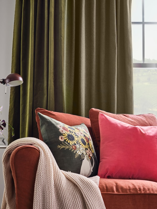 Light red sofa with cushions in different colors and a pale pink throw. Green curtains hang at the window behind.