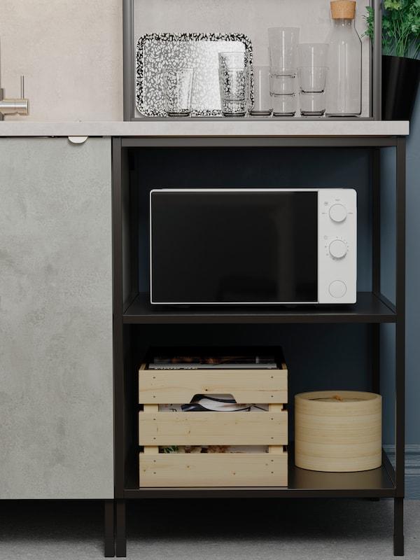 V otevřených policích pod kuchyňskou pracovní deskou je umístěná mikrovlnná trouba a dřevěné krabice. Nachází se vedle skříňky s šedými dvířky.