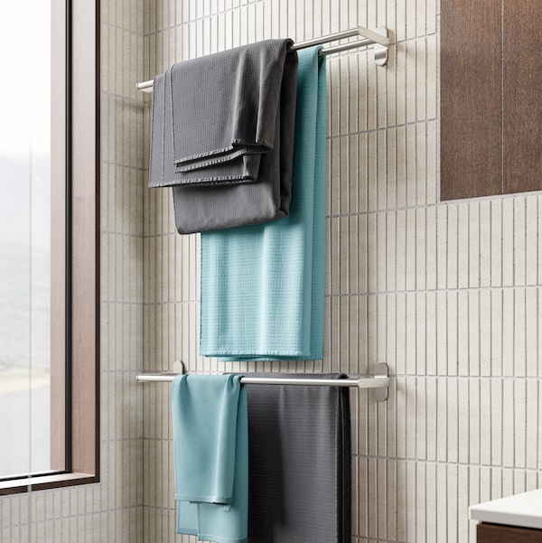 Close-up of a bathroom wall with towel rails, with grey and blue-green towels.