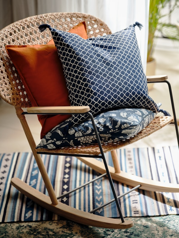 A GRÖNADAL rocking chair cradling assorted patterned cushions and standing on a multicolor rug.