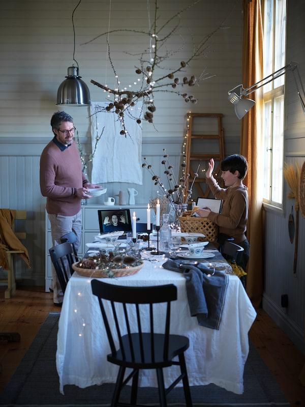 Ett bord som är dukat för fest där en man och en pojke tillsammans förbereder inför kvällens festmåltid.