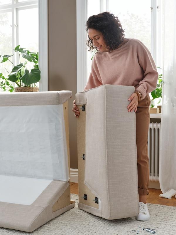 Kobieta montująca bok sofy w beżowym pokryciu do modułu oparcia.