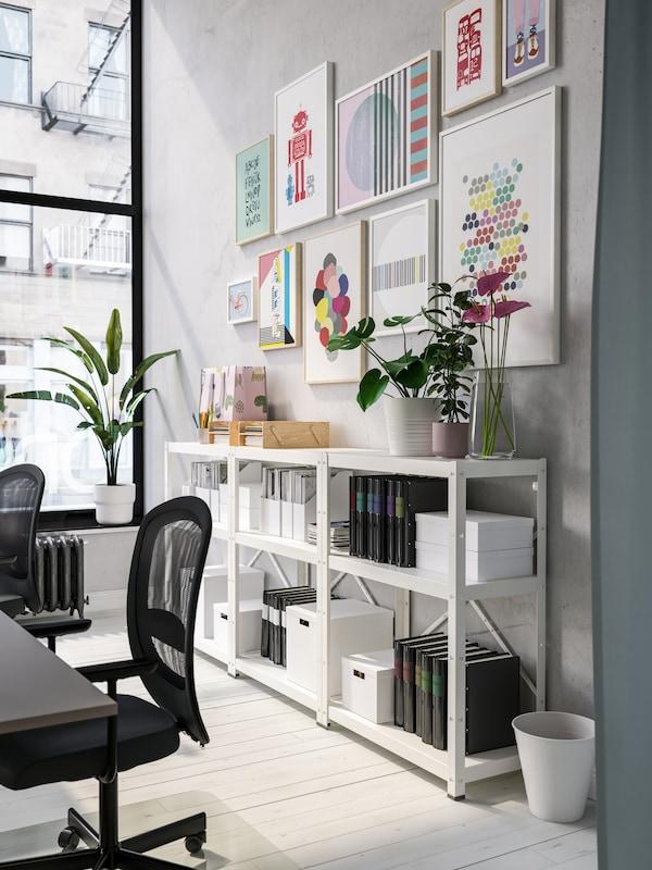 Scaffali bianchi con portadocumenti neri e scatole bianche, stampe colorate incorniciate alla parete, sedie da ufficio nere.