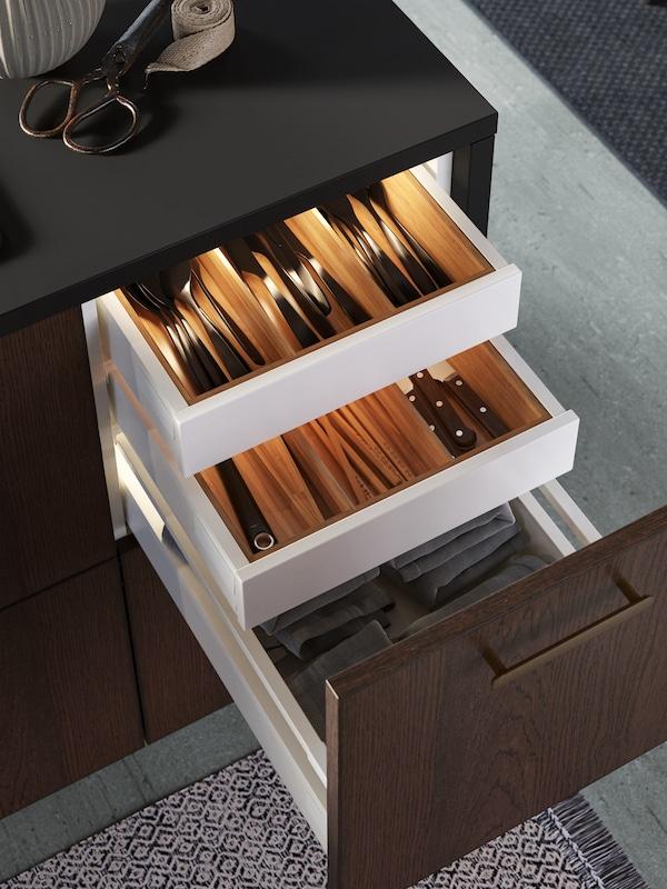 Otvorené zásuvky na kuchynskom ostrove, v ktorých sú úhľadne usporiadané drevené prieradky s príborom a zabudované osvetlenie.