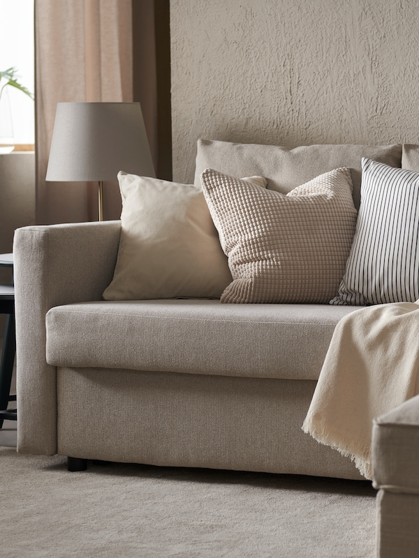 A throw and three cushions with different patterns lie on a beige FRIHETEN sofa. There is a lamp beside the sofa.
