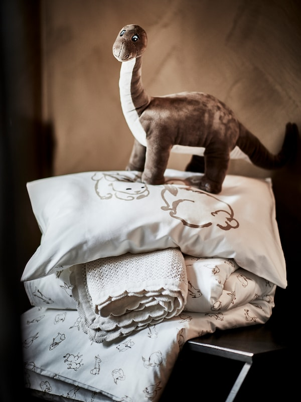 A JÄTTELIK soft toy shaped like a dinosaur stands on top of a pillow and duvet in RÖDHAKE covers and a GULSPARV blanket.