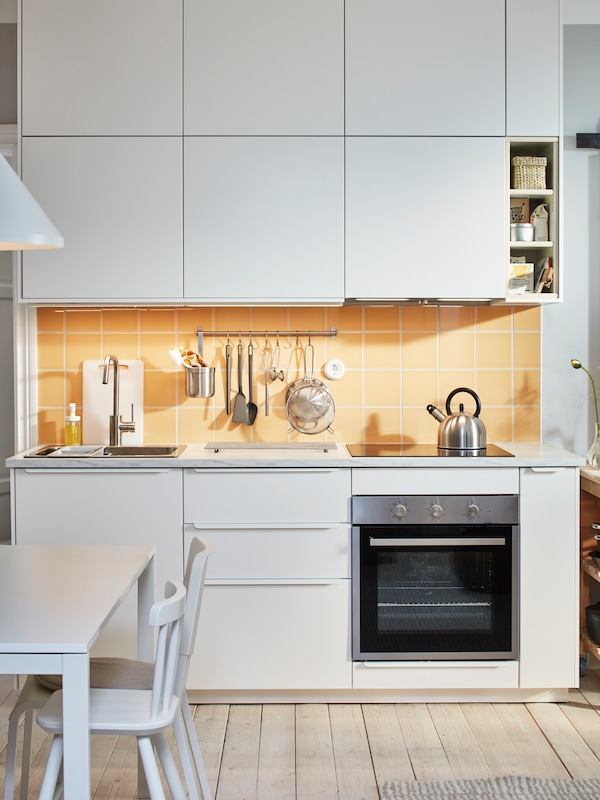 Una piccola cucina bianca con mobili base e pensili bianchi, piastrelle gialle e un forno.