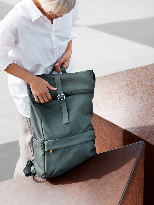 A woman who is wearing a white blouse and gray trousers adjusts the top of an olive-green DRÖMSÄCK backpack.