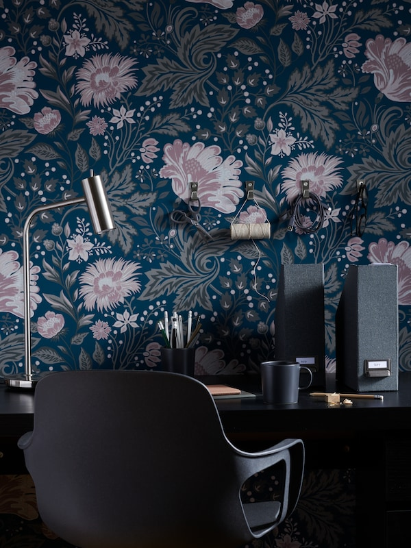 A black chair sitting at a desk with dark blue wallpaper with flower patterns.