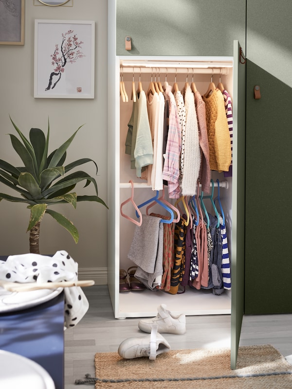 An open wardrobe door showing children's clothes hanging from two rails, and integrated lighting that's turned on.