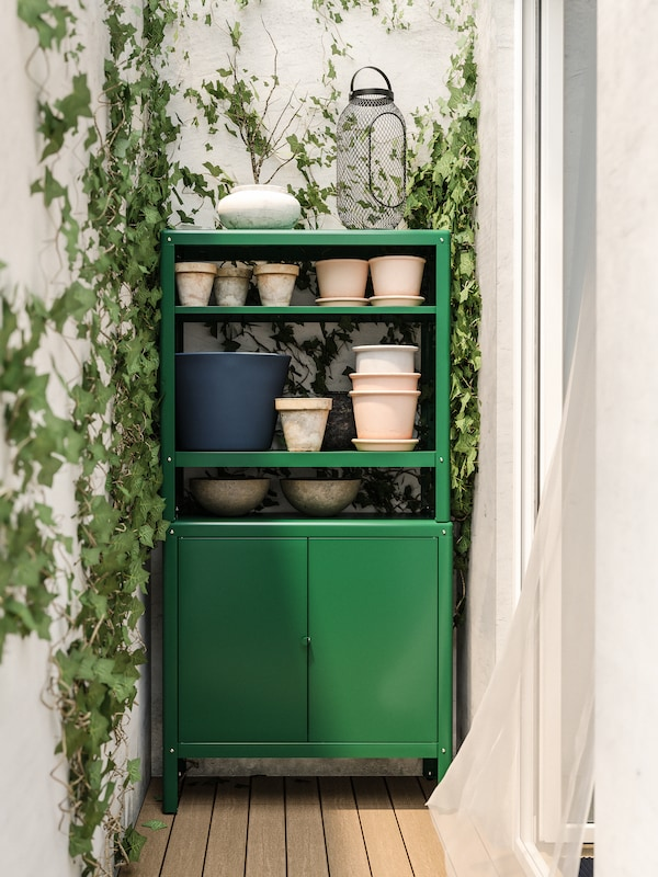 A green storage cabinet with plant pots on the shelves, against a white wall with green ivy.