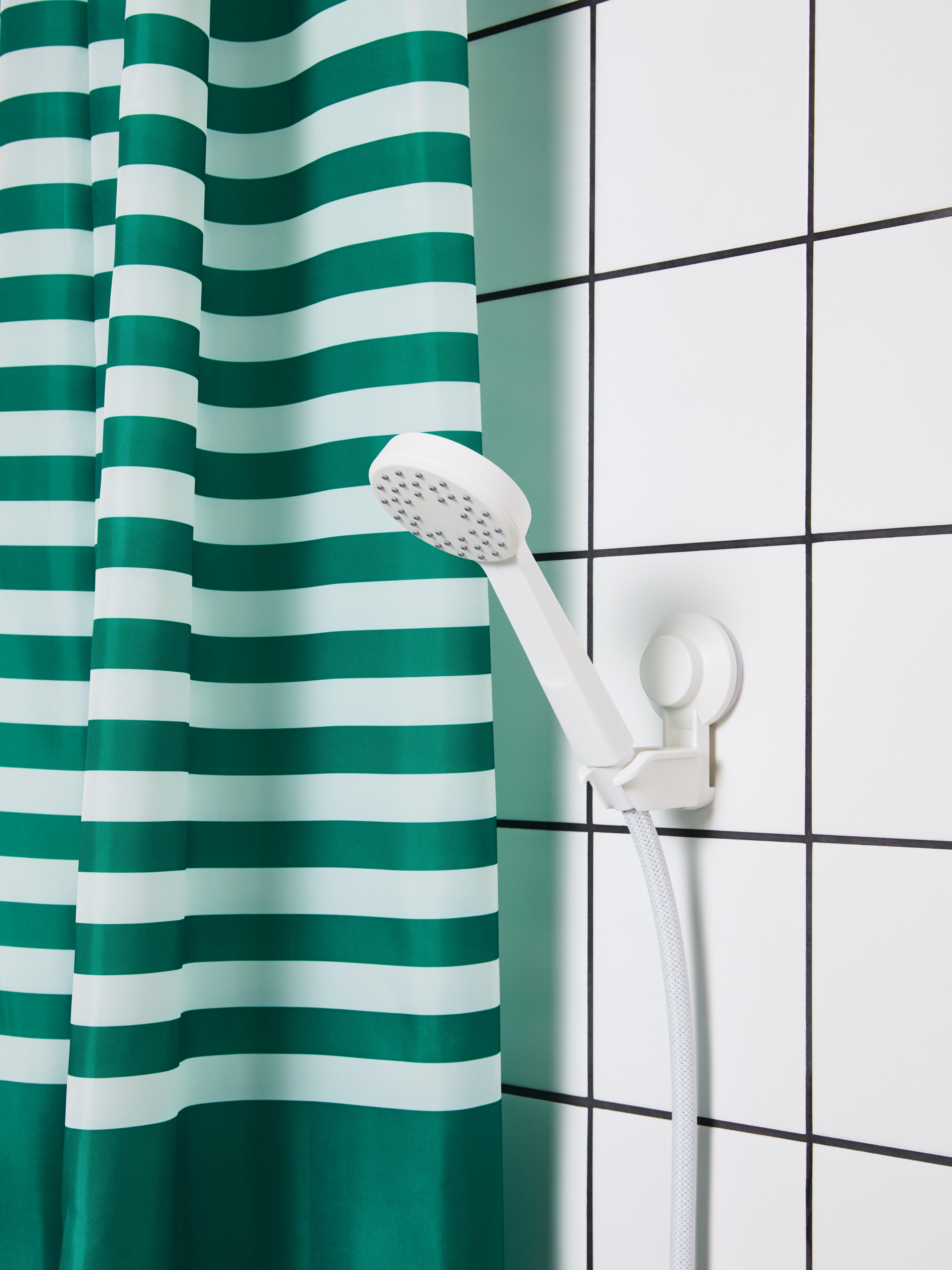 Baldosa zuriko bainugela, esku-dutxa zuridun zuria, hodi malgu zuria eta dutxa-gortina marradun zuri eta berdeak.