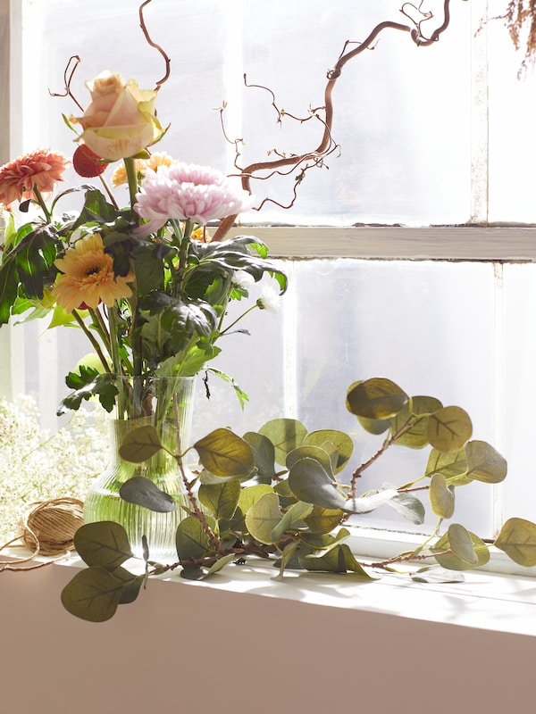 SMYCKA artificial eucalyptus leaves on a sunlit windowsill next to a clear-glass PÅDRAG vase with colourful flowers.