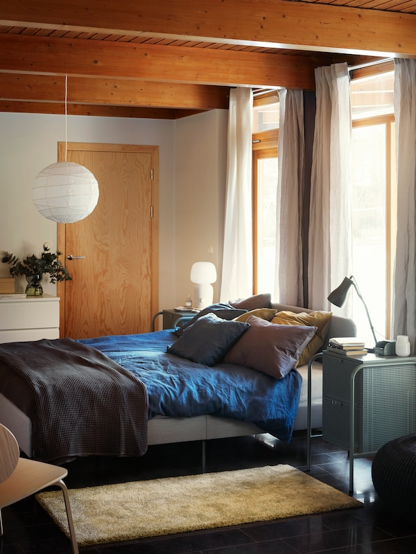 A bedroom with a light SLATTUM upholstered bed frame, blue bed linen, a throw, several pillows and a golden yellow rug.