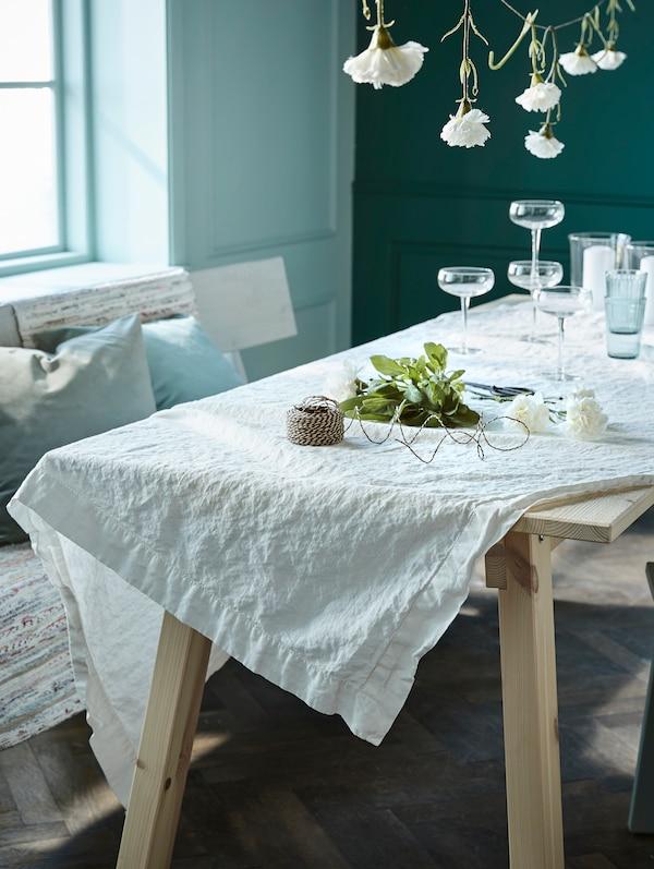 Ein Tisch mit einer GULLMAJ Tischdecke. Darauf sind die STORHET Sektschalen und andere Gegenstände zu erkennen. Über dem Tisch hängen kopfüber ein paar Blumen.