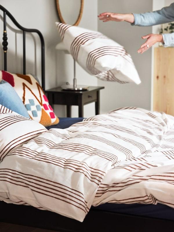 Egy személy ágyat készít fehér/barna csíkos SMALFRÄKEN paplanhuzattal, valamint különböző színű párnahuzattal és párnákkal.