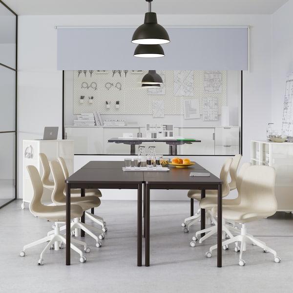Črna miza z bež vrtljivimi stoli stoji v pisarni, viseča svetila in tabla s predstavitvijo na skrajni steni.