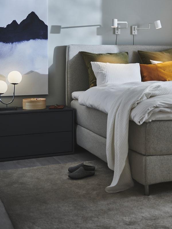 Postel s bílým ložním prádlem a žlutými a tmavě zelenými polštáři. Bílé nástěnné lampy nad postelí a vedle stojící zásuvkový díl.