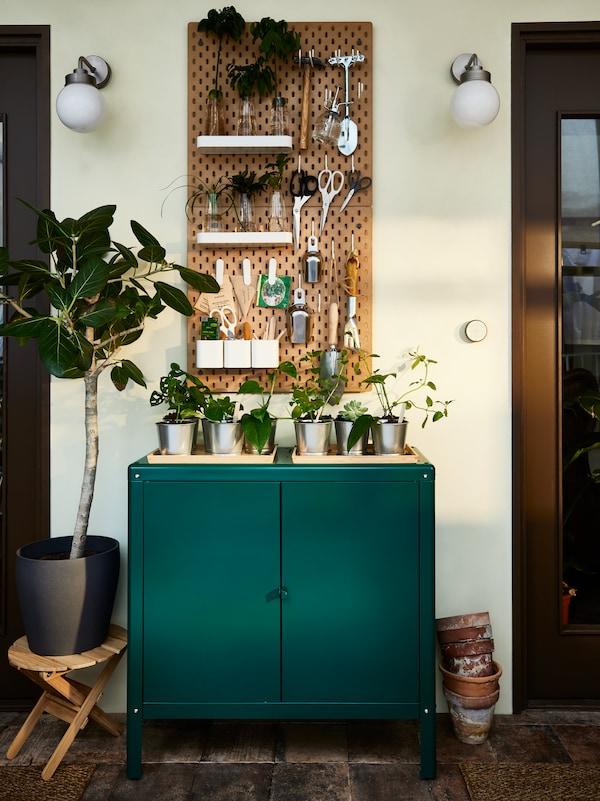 ألواح تعليقSKÅDIS مع أغراض عناية بالحدائق وخزانة فولاذ خضراء مع شتلات من أعلى، ومصباحي حائطFRIHULT ونبات كبير.