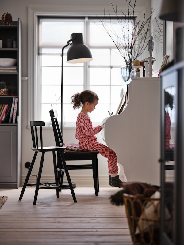A girl sits by a piano on a brown-black INGOLF chair. A HEKTAR floor lamp and a black AGAM junior chair stand nearby.