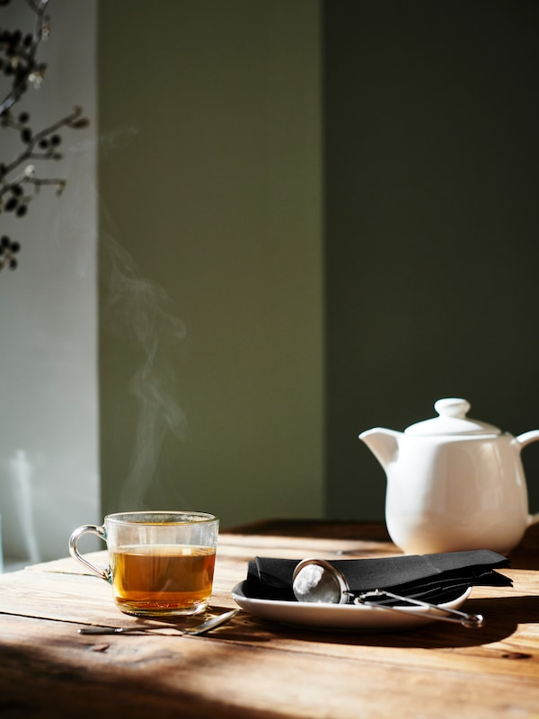 A small white teapot and a steaming clear glass cup of tea.