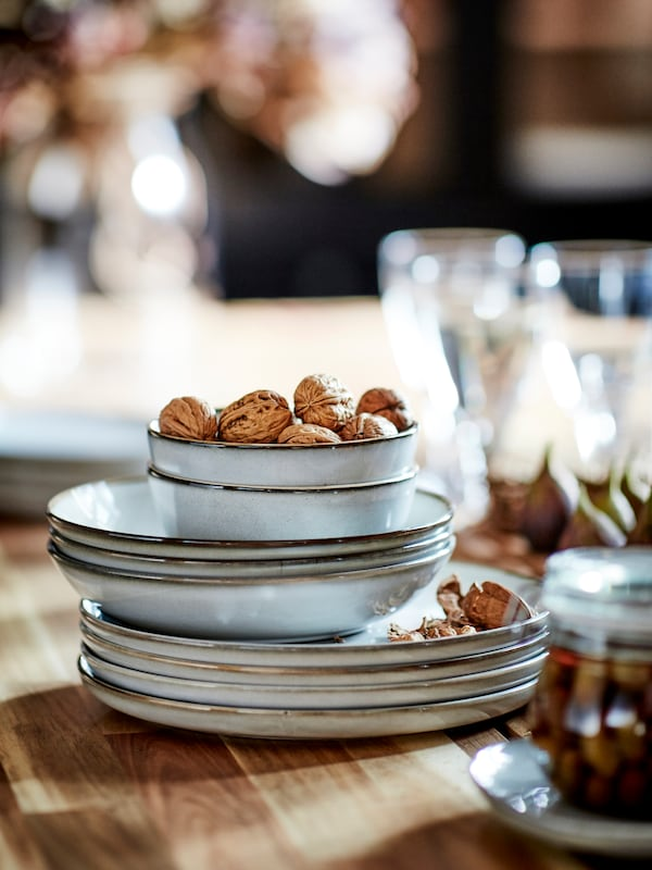 GLADELIG deep plates, bowls and plates in gray with a sandy glaze are stacked together. The top bowl contains walnuts.