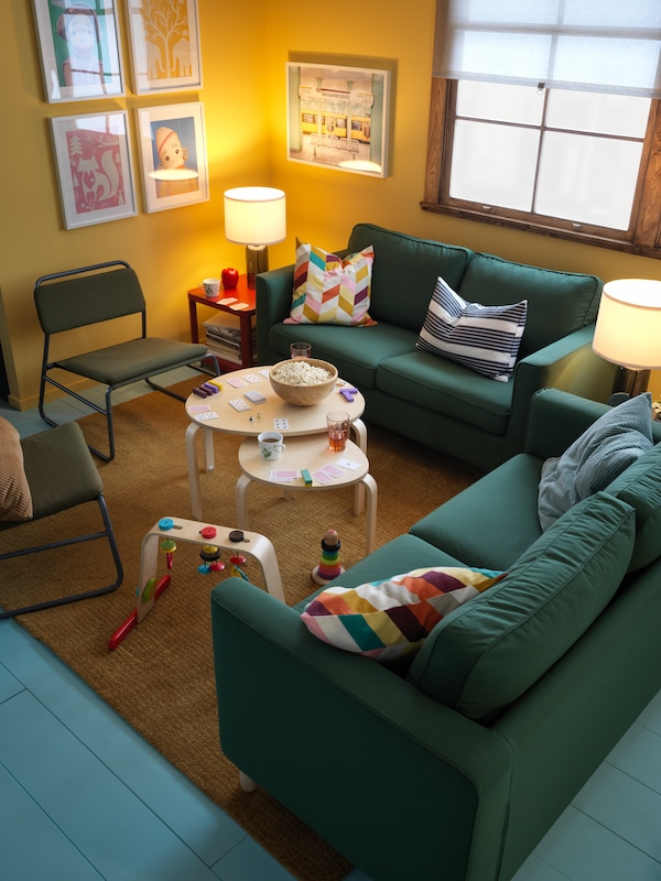 Two nest tables and LEKA baby gym on a rug in between two green PÄRUP sofas and two LINNEBÄCK easy chairs.
