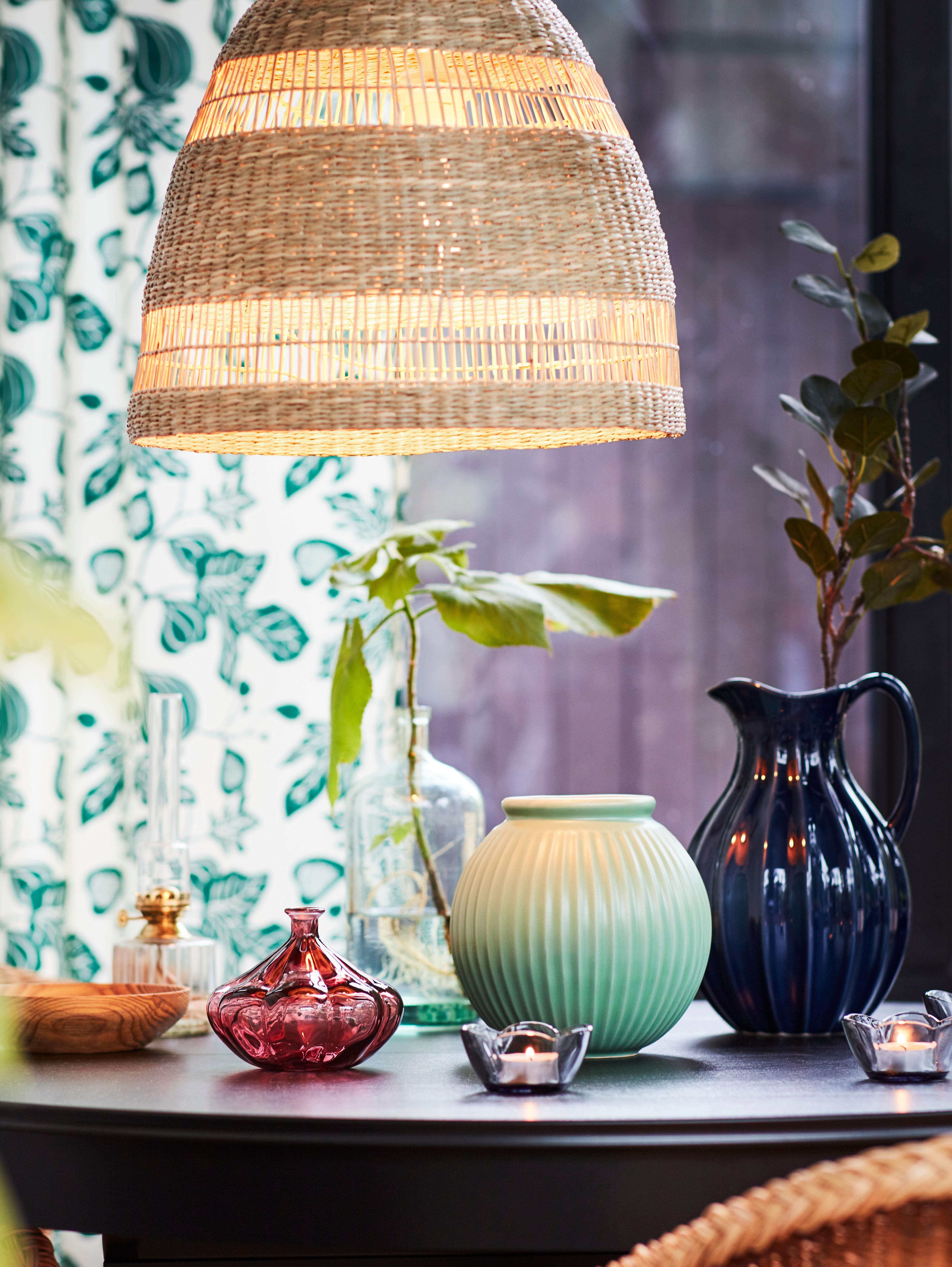 Un paralume per lampada a sospensione TORARED realizzato con piante erbacee intrecciate a mano è appeso sopra un tavolo rotondo sul quale sono disposti diversi vasi e candele.