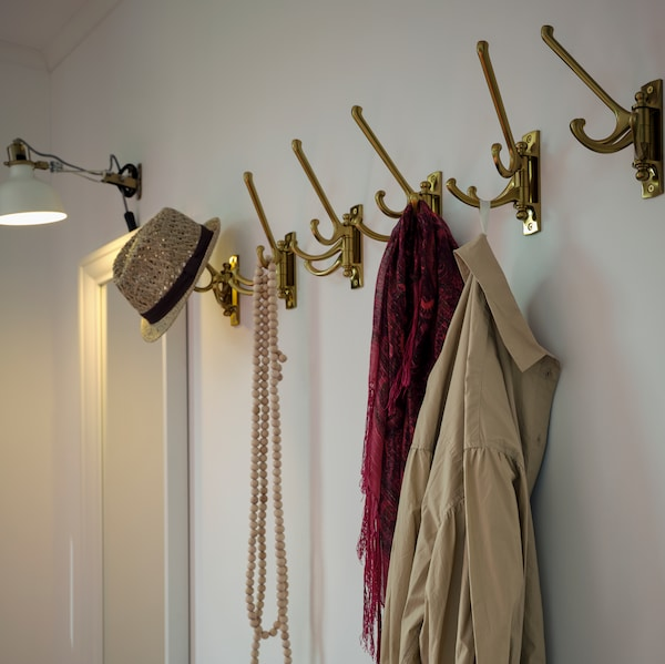 A mirror and wall lamp are mounted on a wall, next to a row of KÄMPIG 3-armed swivel hooks holding clothes and a hat.