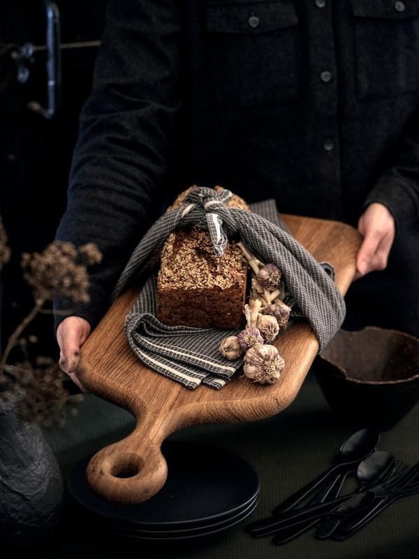 Osoba ukazuje dubové prkénko ARTISTISK sdomácím chlebem zabaleným do šedé utěrky MARIATHERES.