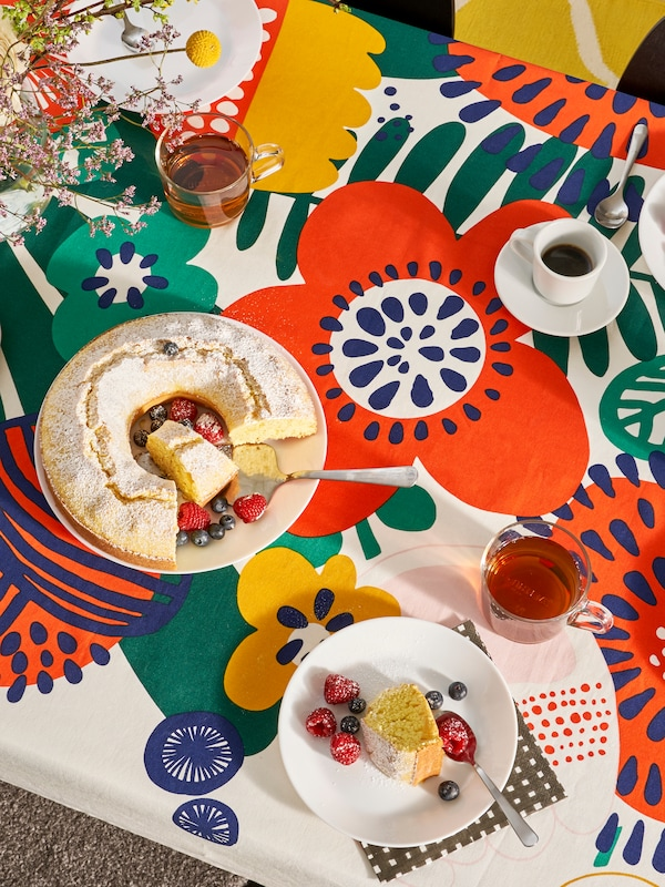 A table that has a bright flower-patterned tablecloth, plates, glasses, cups and a cake on it.