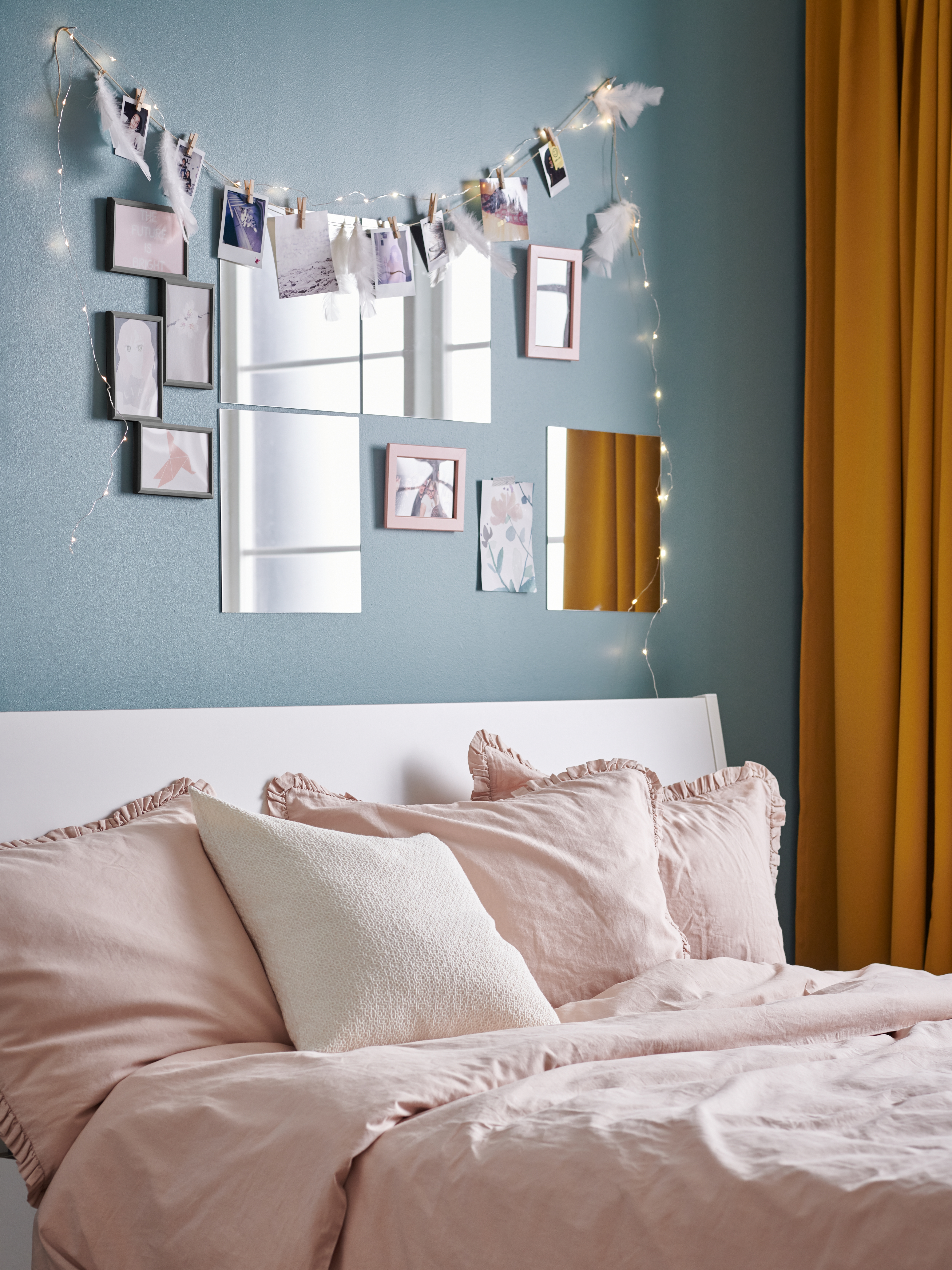 A bed with the wall over its headboard covered with a decorative display of YLLEVAD frames, LOTS mirrors and lighting chains.