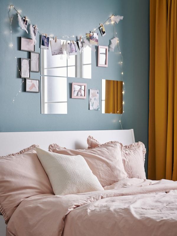 Ljusblå vägg dekorerad med speglar och ramar.