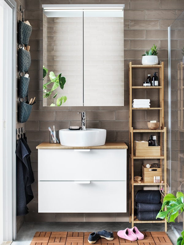 A two door mirror cabinet above a white wash-stand with a bamboo countertop. A shelving unit in bamboo stands next to it.